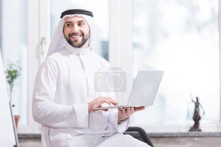 Arabian businessman holding laptop in modern office