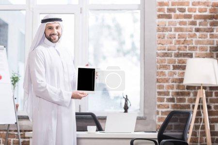 Photo pour Homme d'affaires saoudien tenant la tablette numérique de bureau moderne - image libre de droit
