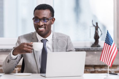 African american businessman holding cup with drink in modern office