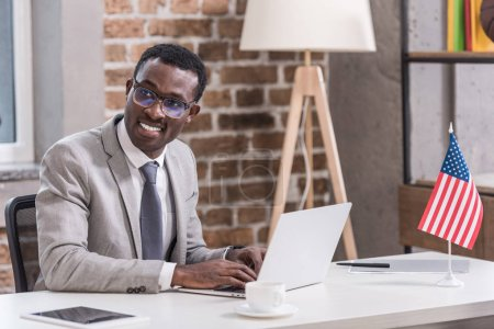 African american businessman using laptop and smiling in office