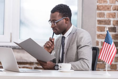 African american businessman holding folder and sitting at office desk