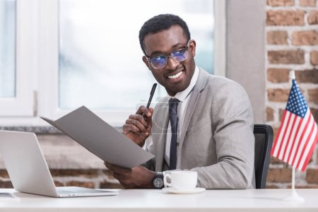 African american businessman holding folder and pen in office