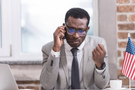 African american businessman talking on smartphone in modern office