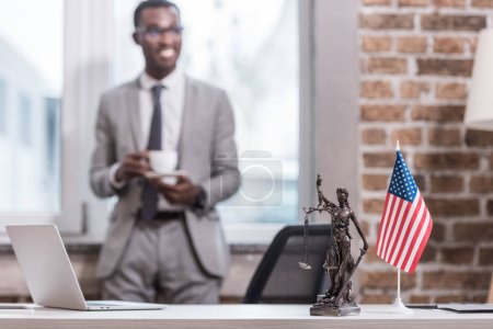 Office desk and objects with african american businessman on background