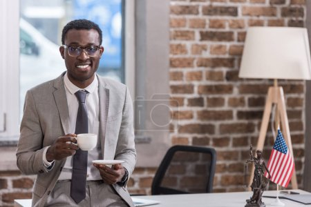 African american businessman drinking coffee in office