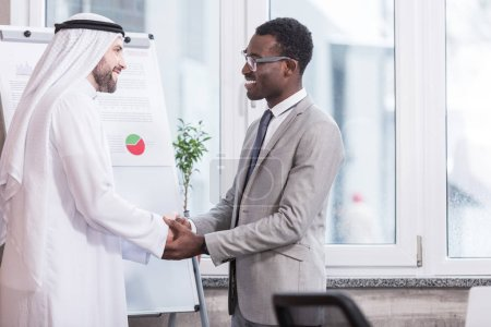 Businessmen smiling and shaking hands in modern office