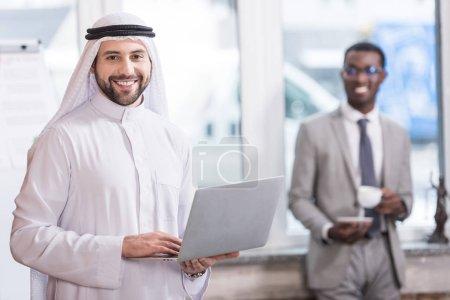 Photo pour Homme d'affaires saoudien tenant ordinateur portable au bureau avec des partenaires africains américains sur fond - image libre de droit