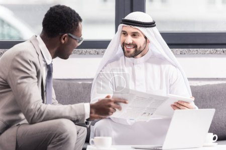 Multicultural businessmen talking and smiling in modern office