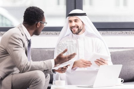 Multicultural businessmen having discussion and holding gagets in office