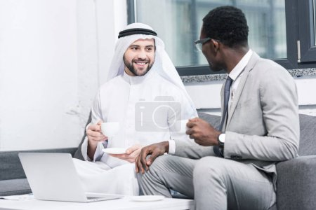 Multicultural businessmen drinking coffee and taking in office