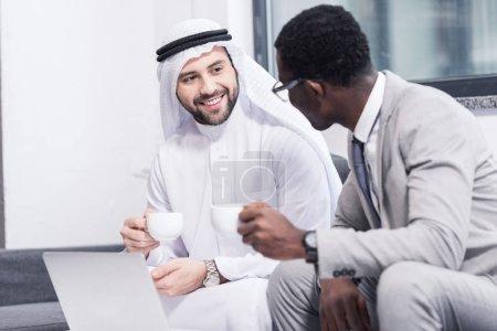 Photo pour Hommes d'affaires multiculturelles de boire du café et de parler au bureau - image libre de droit