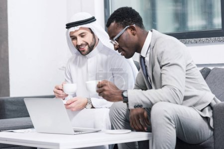 Multicultural businessmen holding cups and looking at laptop in modern office