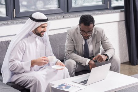 Photo for Multicultural businessmen sitting and looking at laptop in modern office - Royalty Free Image