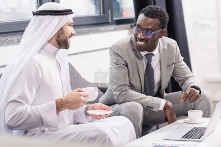 Arabian businessman holding cup and having meeting with african american partner