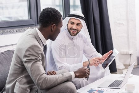 Arabian businessman smiling and using digital device in modern office