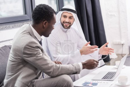 smiling arabian businessman and african american partner talking in office