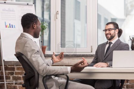 handsome multiethnic business partners sitting at office desk