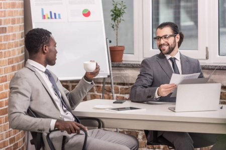 Photo for Smiling multiethnic businessmen sitting at office table, drinking coffee and having discussion - Royalty Free Image