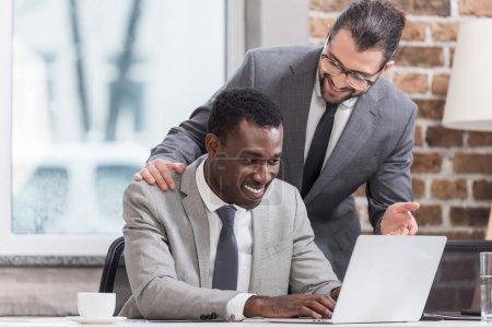 Photo pour Homme d'affaires afro-américain tapant sur le clavier de l'ordinateur portable tout en souriant partenaire lui parlant - image libre de droit