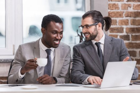 smiling multicultural businessmen drinking coffee and looking at laptop in office