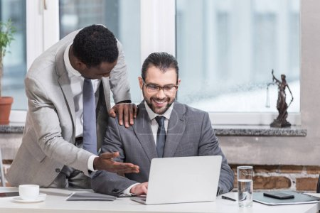 african american businessman putting hand on partners shoulder and pointing at laptop in office