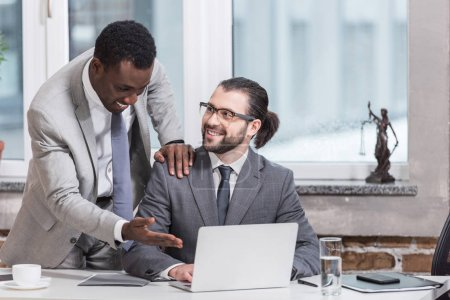 smiling african american businessman putting hand on partners shoulder and pointing at laptop in office