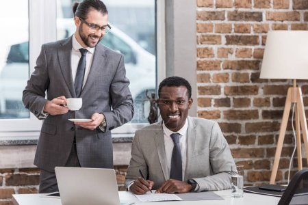 african american businessman signing document while partner drinking coffee in office