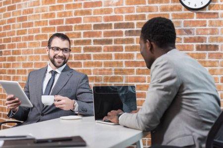 homme d'affaires avec tablette numérique et afro-américain associé à l'ordinateur portable en regardant l'autre dans le Bureau de sourire