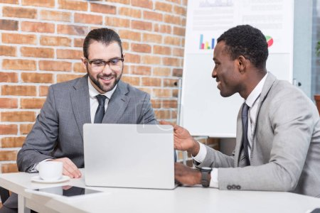smiling multiethnic businessmen sitting at table with laptop and having discussion in office