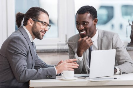 Photo for Smiling multicultural businessmen sitting at table with laptop and having discussion - Royalty Free Image