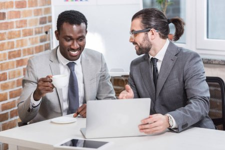 handsome businessman pointing at laptop and smiling african american partner drinking coffee in modern office