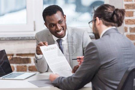 Photo pour Hommes d'affaires multiethniques, signature du contrat au bureau - image libre de droit