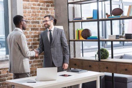 Photo pour Hommes d'affaires multiethniques se serrant la main dans le bureau moderne - image libre de droit