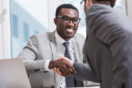 close up view of smiling multiethnic businessmen shaking hands in office