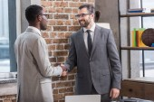 smiling handsome businessman and african american partner shaking hands in office