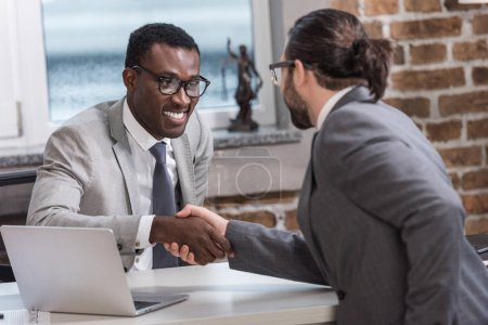 smiling african american businessman and business partner shaking hands in office