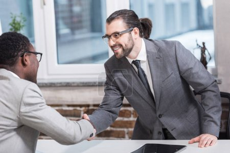 Photo for Smiling multiethnic business partners shaking hands at office table - Royalty Free Image