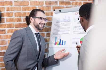 Photo for Multiethnic businessmen smiling and talking in front of flip chart with documents and graphs - Royalty Free Image