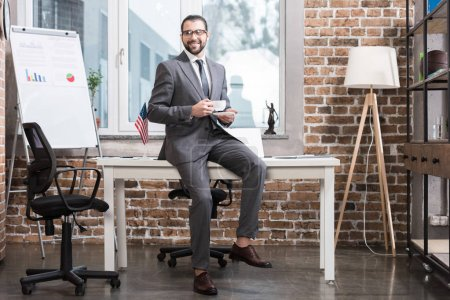 handsome businessman sitting at table and holding coffee cup in office