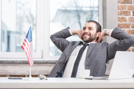 successful businessman with hands on head sitting at office desk
