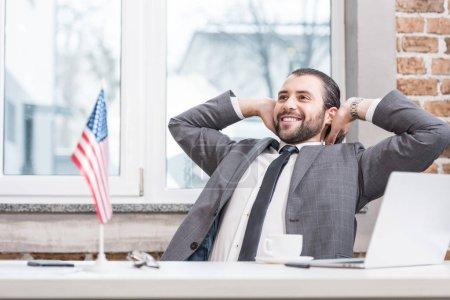 homme d'affaires prospère avec les mains sur la tête, assis au bureau