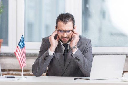 disappointed businessman sitting at office desk with laptop and american flag