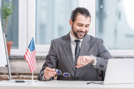 smiling businessman sitting at table with laptop and little american flag and looking at watch