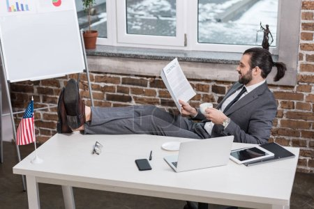 smiling businessman sitting at table, putting feet up and reading contract in office