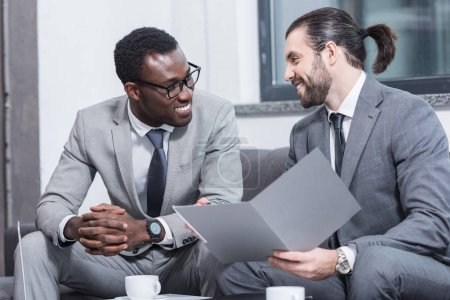 smiling multiethnic business partners sitting on couch and talking in office