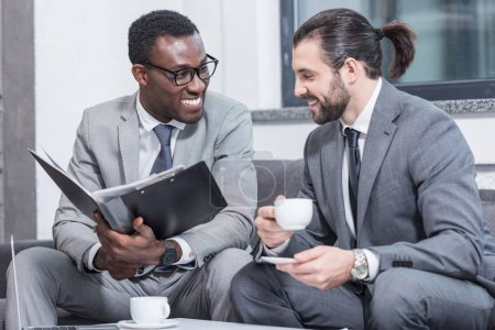 successful multiethnic businessmen sitting on couch, smiling and drinking coffee in office