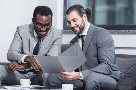 smiling multiethnic businessmen reading document in office