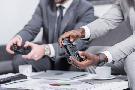 Photo for Cropped view of multiethnic businessmen sitting at table with documents and holding gamepads - Royalty Free Image
