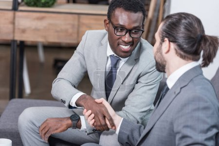 Photo for Multiethnic business partners sitting on sofa and shaking hands - Royalty Free Image