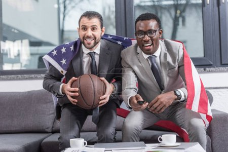 multiethnic businessmen with american flag on shoulders watching basketball match in office